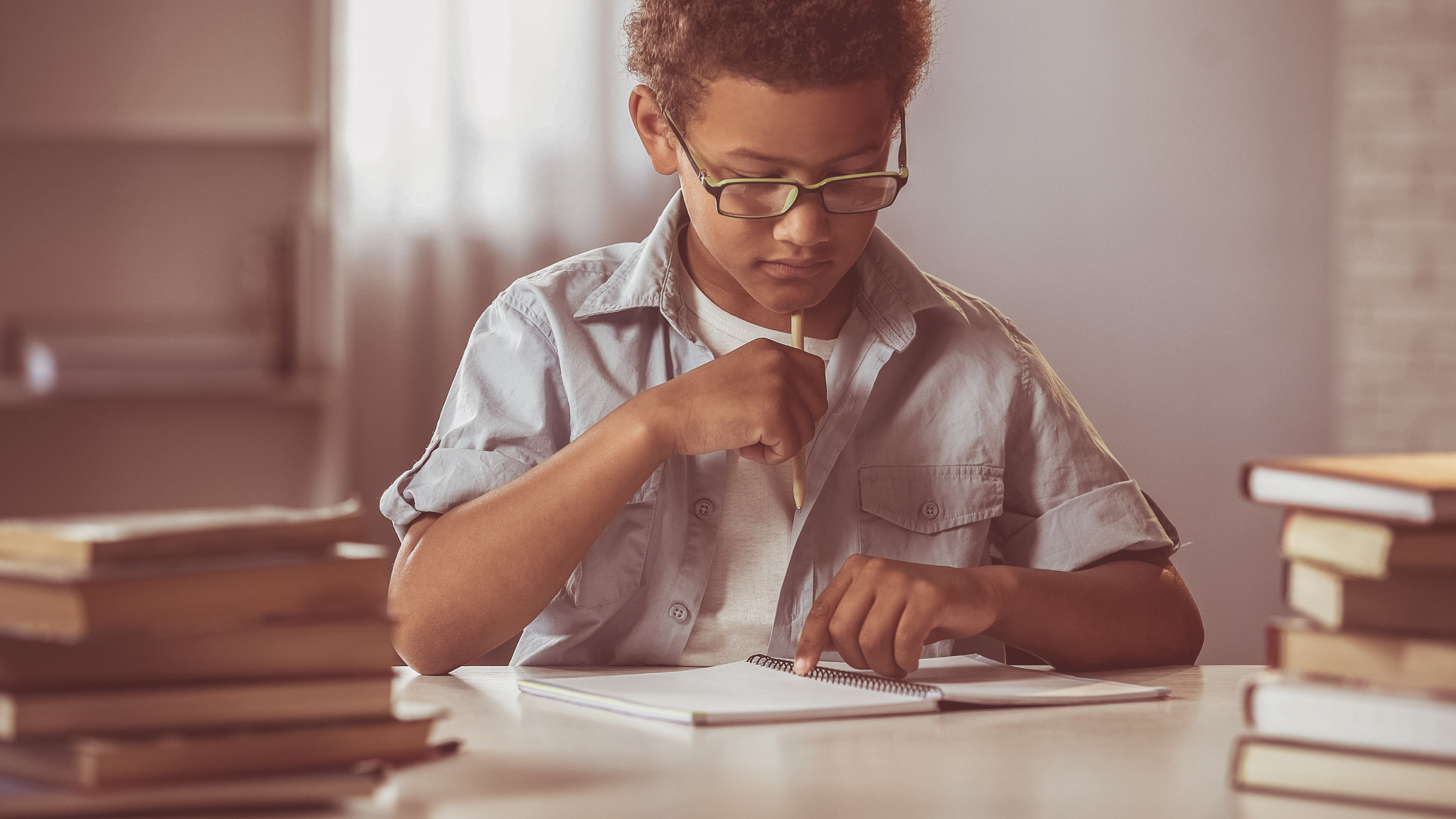 Thinking boy sitting with blank notebook table, writing homework